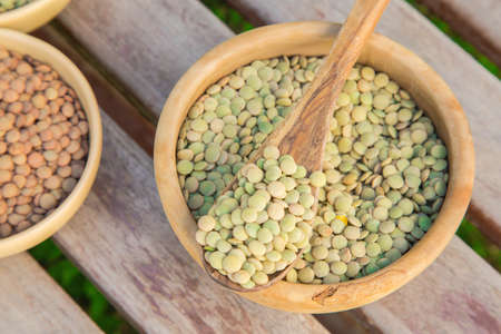 Dried green lentils on the olive tree wooden spoon photo