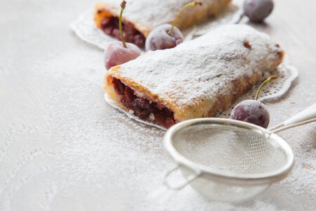tea strainer: Traditional romanian and moldovan dessert - invertita.Baked rolled thin dough stuffed with sour cherries. Frozen sour cherries and a tea strainer in the background.The dessert placed on the wooden surface. Stock Photo