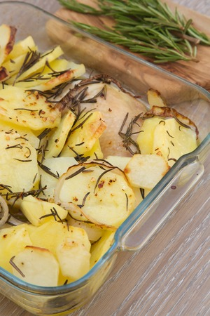 baked potatoes: Baked potatoes with chicken and rosemary in the glass mould. Fresh rosemary on the wooden cutting board in the background