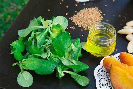 rapunzel: Cornsalad and some other ingredients for a salad on the black wooden surface