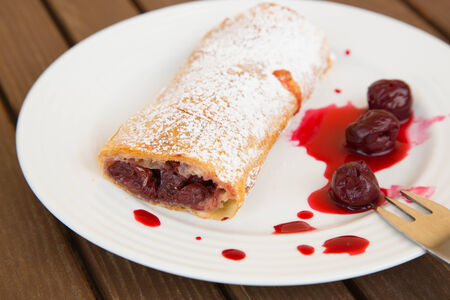 moldovan: Traditional romanian and moldovan dessert - invertita.Baked rolled thin dough stuffed with sour cherries. Dessert on the white plate.Close up