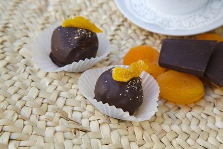 woven surface: Trufa de chocolate hecho a mano con albaricoques secos en la superficie tejida. Orejones, trozos de chocolate negro y una taza de caf� en el fondo Foto de archivo