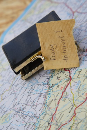 Message left at a small wallet:Ready to travel? Items are placed on the road map Stock Photo