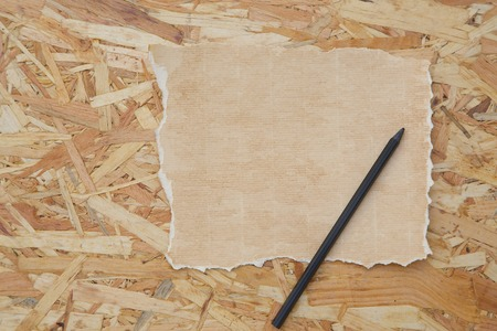distressed paper: A sheet of distressed carton paper and a black pencil on the wooden surface. Free space for a text Stock Photo