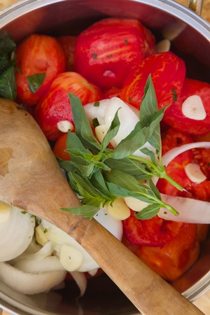 Prepared food ingredients for cooking Italian tomato sauce - salsa- in the pot . Close up photo