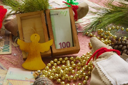 Money present in a small wooden box with a festive background photo