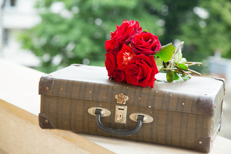 farewell: Vintage suitcase and a bunch of red roses on the balcony wall with green background Stock Photo
