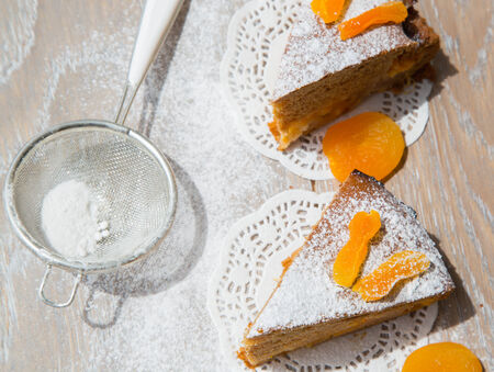 tea strainer: Two pieces of apricot pie, decorated by dried apricots on the wooden surface. Tea strainer in the background.top view Stock Photo
