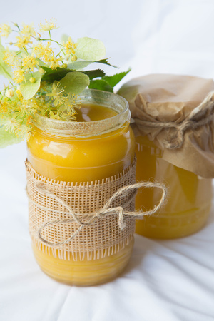 linden flowers: Two glasses of linden honey and fresh linden flowers