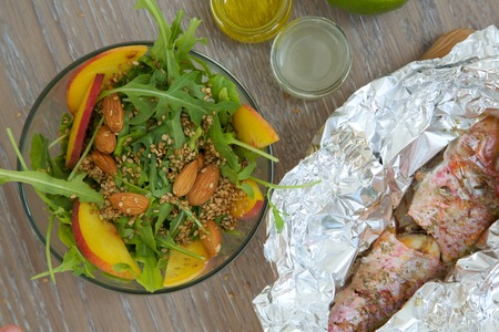 goatfish: Vitamin salad- rucola with almond, peach and sesame seeds in glass dish and baked fish in the aluminium foil from the right side. Top view