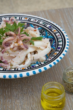 selenium: Marinated squid salad with fresh parsley in the traditional Tunisian plate. Oregano, olive oil and squeezed lemon in the background Stock Photo