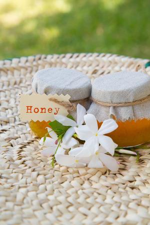 woven surface: Dos peque�os vasos de miel jasmin en la superficie tejida Foto de archivo