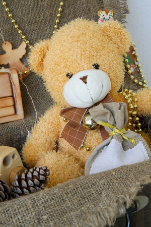 old items: Christmas teddy bear in an old case with decorative items for a festive season Stock Photo