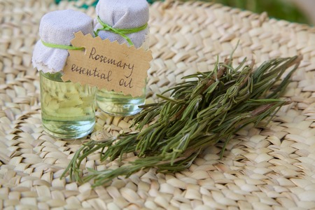 relieving pain: Rosemary essential oil and rosemary branchlets in the background