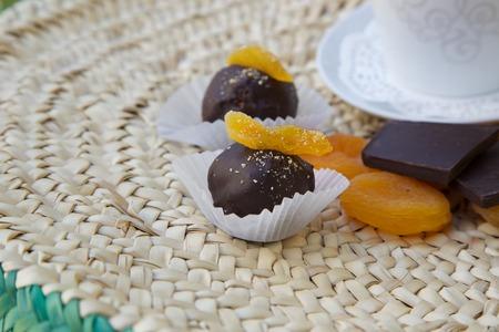 woven surface: Trufa de chocolate hecho a mano con albaricoque seco sobre una superficie tejida. Orejones, trozos de chocolate y una taza de t� en el fondo