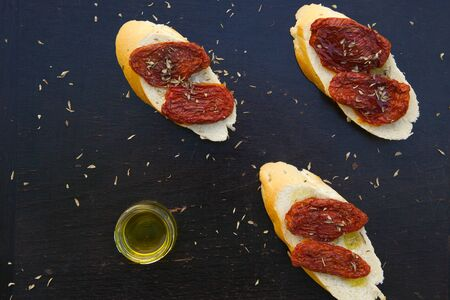 lycopene: Flavorful starter - sun-dried red tomatoes with oregano and olive oil on the pieces of French baguette