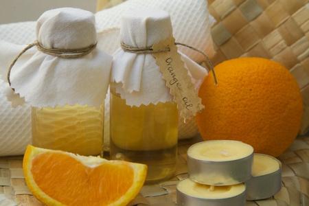 woven surface: Botellas de aceite de naranja en una superficie tejida. Naranja y vela con fragrancde naranja en el fondo