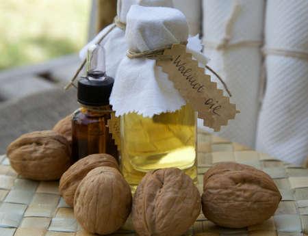 woven surface: Botella de aceite de nuez en la superficie tejida. Nueces en el fondo