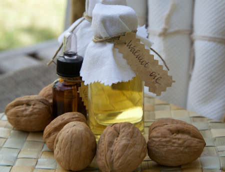 fair skin: Bottle of walnut oil on the woven surface. Walnuts in the background