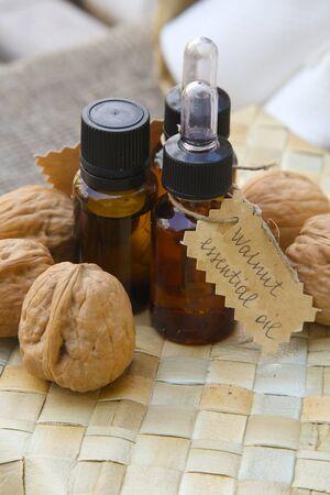 woven surface: Botella de aceite esencial de nuez en la superficie de tejido. Nueces en el fondo