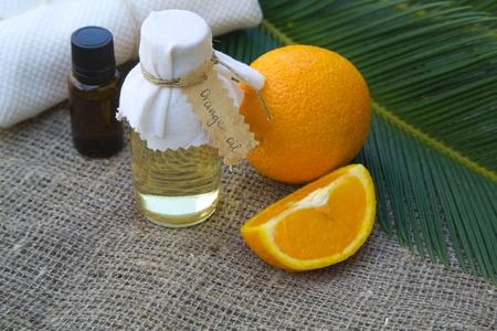 Bottle of orange oil. Fresh oranges in the background