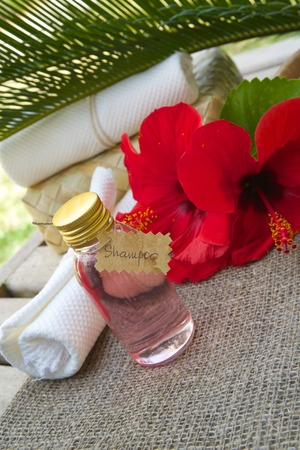 stimulator: A bottle of hibiscus shampoo. Flowers of hibiscus in the background