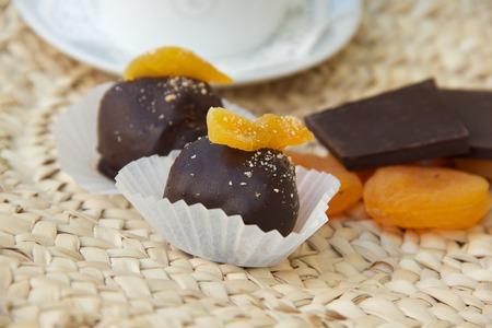 woven surface: Trufa de chocolate hecho a mano con albaricoques secos en la superficie tejida. Albaricoques y trozos de chocolate negro en el fondo secas Foto de archivo