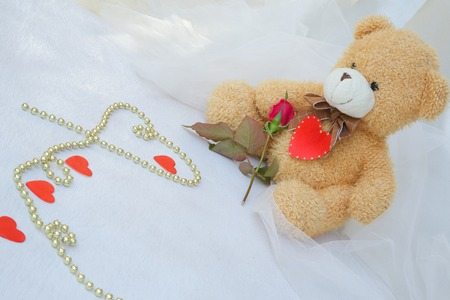 Brown plush Teddy bear with red heart and red rose. Golden like perls on a white wooden surface. photo