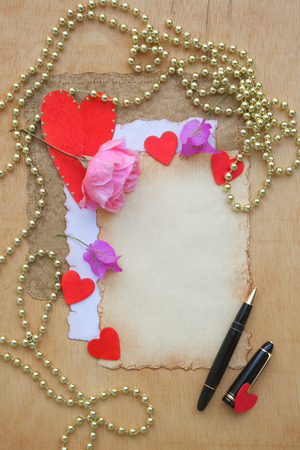 perl: Valentines Day background. Old paper,pink rose,red hearts,violet flowers,black pen,golden perl chain on a wooden surface. Free space for a text