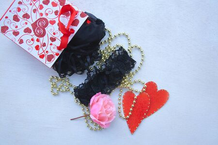 sex appeal: Valentines Day gift for a woman: black lingerie. Red gift bag, pink rose, black lingerie,black garter band,red hearts and golden perl chain on a white surface. Free space for a text