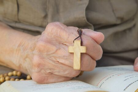 franciscan: A hand of senior woman with wooden cross on a franciscan prayer book Stock Photo