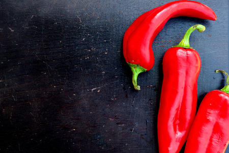 close p: Fresh red hot chill pepper on a black wooden surface. Background. Free space for a text
