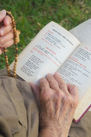 anglican: An open franciscan prayer book and anglican rose beads