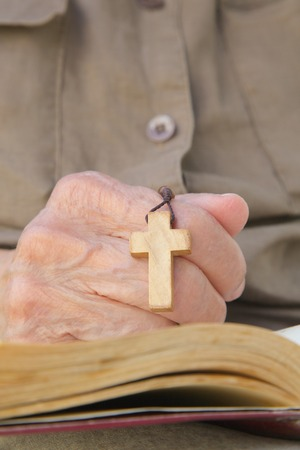 wholeness: A hand of senior woman with wooden cross on a franciscan prayer book Stock Photo
