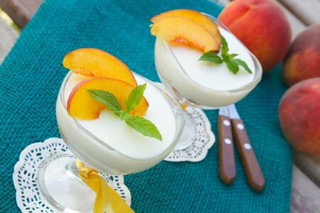 ricotta cheese: Milk dessert - sweet ricotta cheese with peach in a glass dessert bowl. Dessert spoons with wooden handles and fresh peaches in a background.