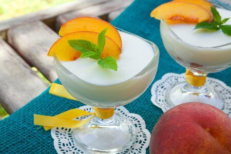 ricotta cheese: Milk dessert - sweet ricotta cheese with peach in a glass dessert bowl. Fresh peach in a background.