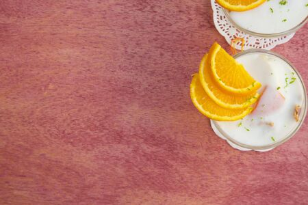 ricotta cheese: Milk dessert - sweet ricotta cheese with oranges- in a glass dessert bowl. Top view. Free space for a text. Stock Photo