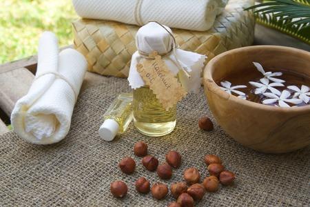 astringent: A bottle of hazelnut oil. Hazelnuts in the background