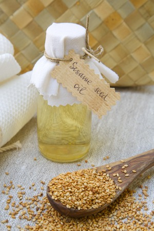A bottle of sesame seed oil. Sesame seeds in the background