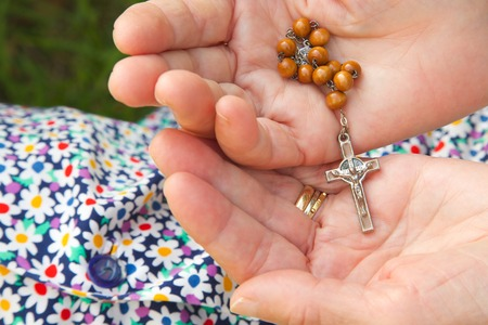 wholeness: Christian prayer beads and crucifix in the hands of old woman