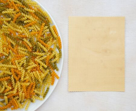 tritium: Raw three-colored Italian pasta. Free space for a text. Background