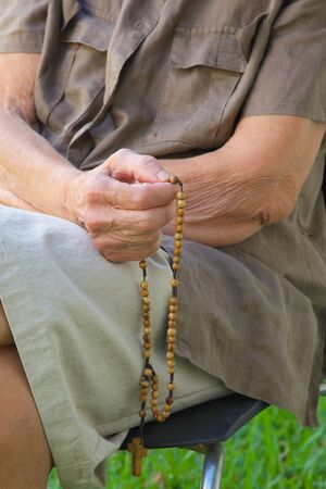 70 80: An old woman between 70 and 80 years old is praying in the garden sitting on the chair and keeping Anglican rosary in her hand. Body parts