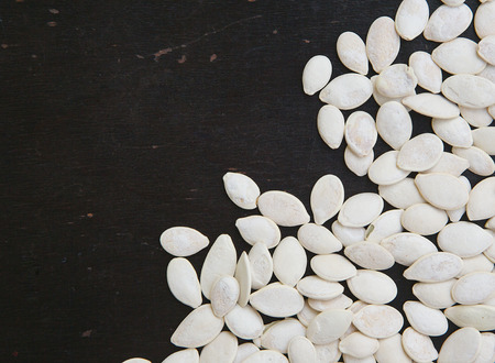 White pumpkin seeds on the black wooden surface. Background. Free space for a text.