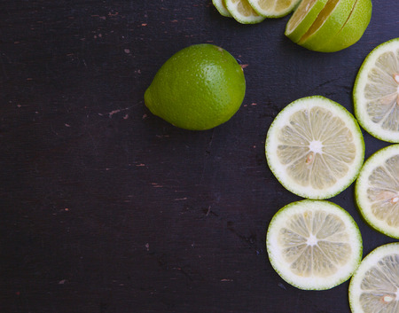 scurvy: Green lemon slices on a black wooden surface. Background. Free space for a text Stock Photo