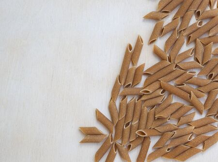 tritium: Whole wheat Italian pasta - penne regate on a white wooden surface. Background. Free space for a text