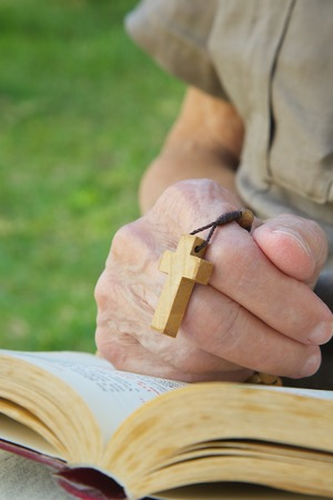 prayer book: A hand of senior woman with wooden cross on a franciscan prayer book Stock Photo