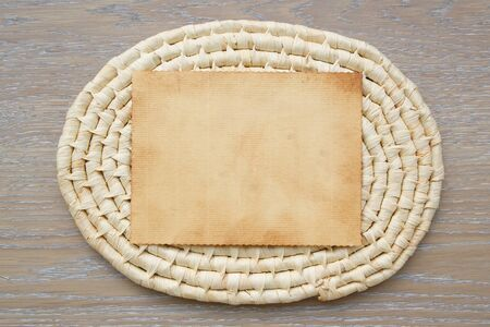 trivet: An old piece of paper on a woven trivet. Free space for a text.