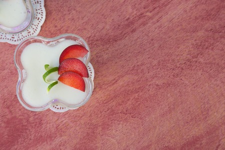 ricotta cheese: Milk dessert - sweet ricotta cheese with plums - in a glass dessert bowl. Top view. Free space for a text.