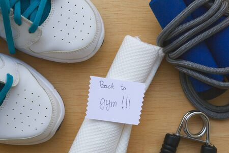 hand gripper: Message written on a piece of paper: Back to gym. Sport items background: snickers,jumping rope,white towel, hand gripper.