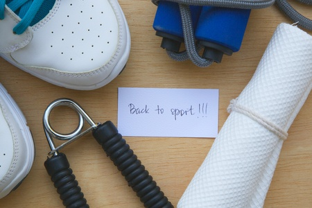 hand gripper: Message written on a piece of paper: Back to sport. Sport items background: snickers,jumping rope,white towel, hand gripper.
